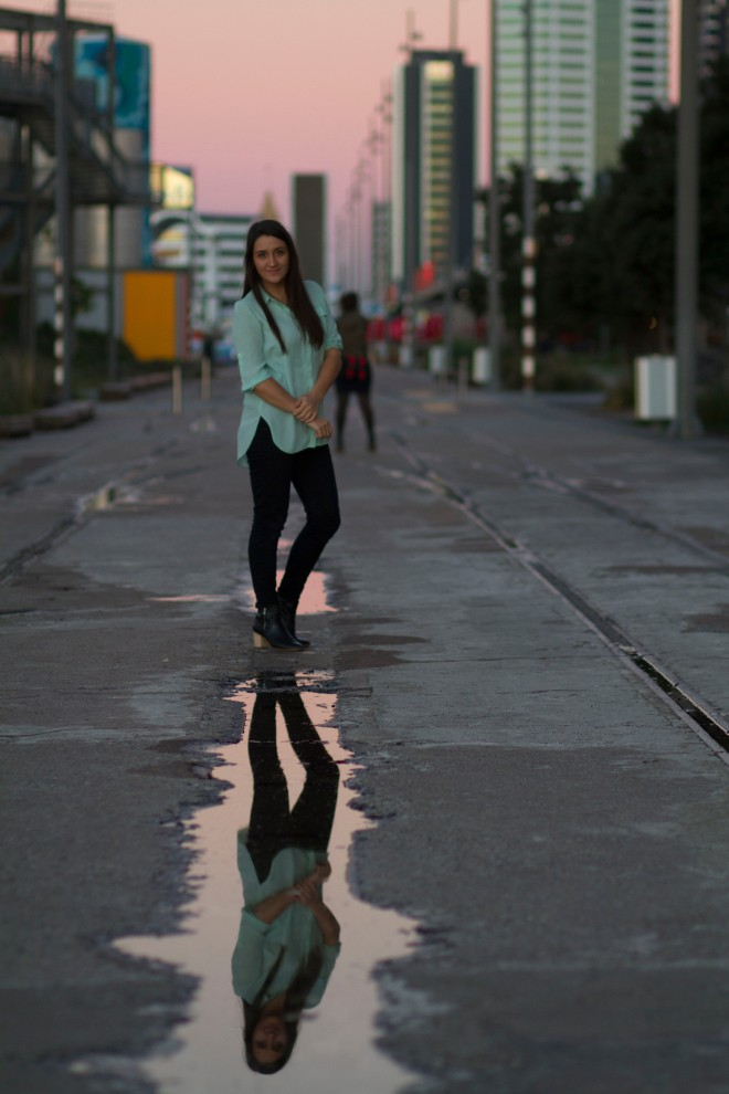 Kera Sherwood-O'Regan photographed at Silo Park, Auckland, by Jason Boberg. Photo shows Kera standing in the middle of a street, with her reflection in a puddle in front of her. She is wearing a mint shirt, black pants and boots, and has long brown hair. She is smiling slightly at the camera.